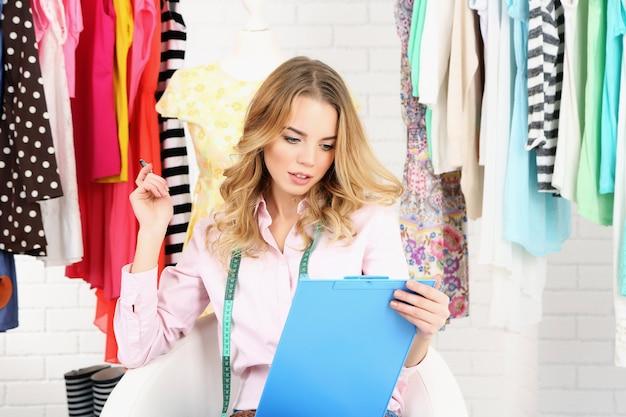 Młoda projektantka mody rysuje nową kolekcję szkiców