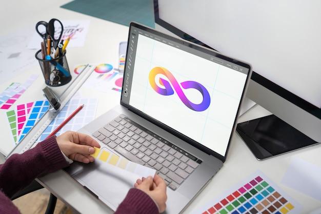 Młoda projektantka pracująca na swoim laptopie
