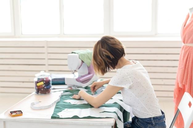 Młoda projektantka robi znaki dla nowego produktu do szycia, siedząc przy stole obok maszyny do szycia. koncepcja kreatywnego biznesu i projektowania.