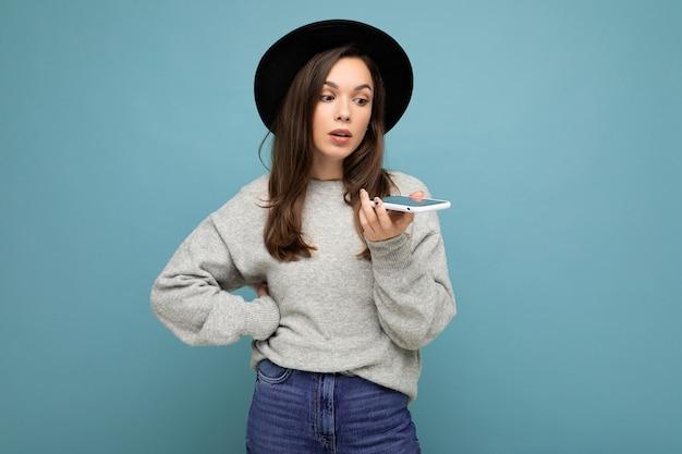 Młoda prosi niezadowoloną brunetkę mówiącą na sobie czarny kapelusz i szary sweter