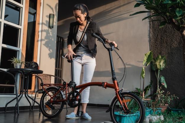 Młoda przedsiębiorca kobieta przygotowuje rower składany z domu