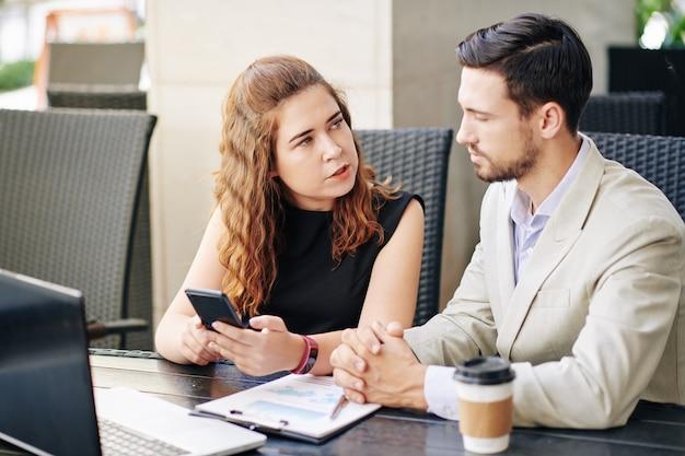 Młoda przedsiębiorczyni pyta współpracownika o radę podczas spotkania w kawiarni