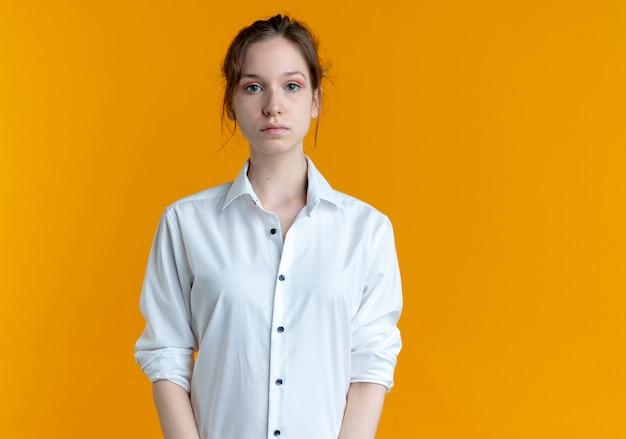 Młoda przekonana blondynka rosjanka patrzy na aparat na białym tle na pomarańczowym tle z miejsca na kopię