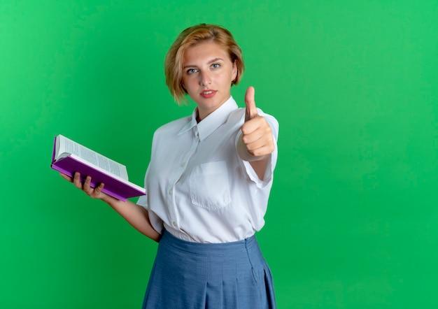 Młoda przekonana blondynka rosjanka trzyma książkę i kciuki do góry na białym tle na zielonym tle z miejsca na kopię