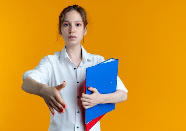 Młoda przekonana blondynka rosjanka trzyma rękę trzymając foldery plików