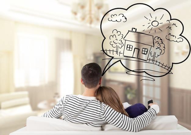 Młoda przemyślana para siedzi na kanapie i myśli o zdobyciu własnego domu