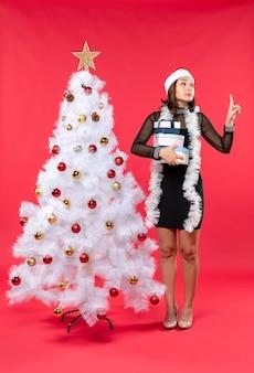 Młoda, przemyślna piękna kobieta w kapeluszu świętego mikołaja i stojąca w pobliżu zdobionej choinki odbiera jej prezenty