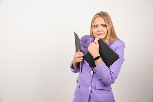 Młoda przerażona kobieta trzyma tabletkę na białym.
