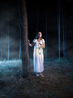 Młoda przestraszona kobieta spacerująca w mglistym nocnym lesie z latarnią