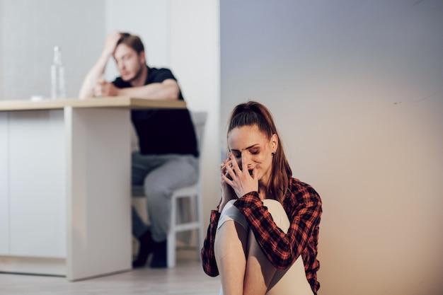 Młoda przestraszona kobieta ze siniakami na twarzy skarży się dziewczynie na telefonie komórkowym siedzącej na podłodze