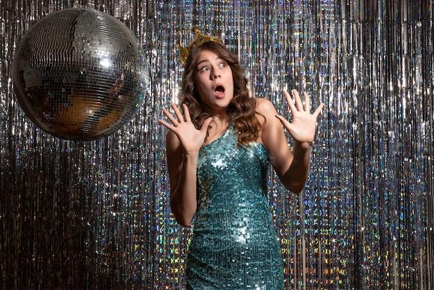 Młoda przestraszona urocza dama ubrana w niebiesko-zieloną błyszczącą sukienkę z cekinami z koroną na przyjęciu
