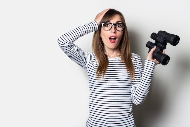 Młoda przyjazna dziewczyna o zdziwionej twarzy trzyma lornetkę na jasnej przestrzeni. transparent. emocjonalna twarz. szok, niespodzianka.