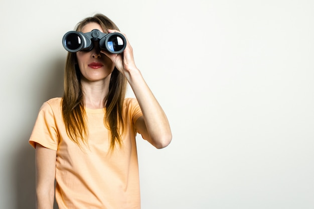Młoda przyjazna dziewczyna patrząc przez lornetkę na jasnej przestrzeni. transparent. emocjonalna twarz.