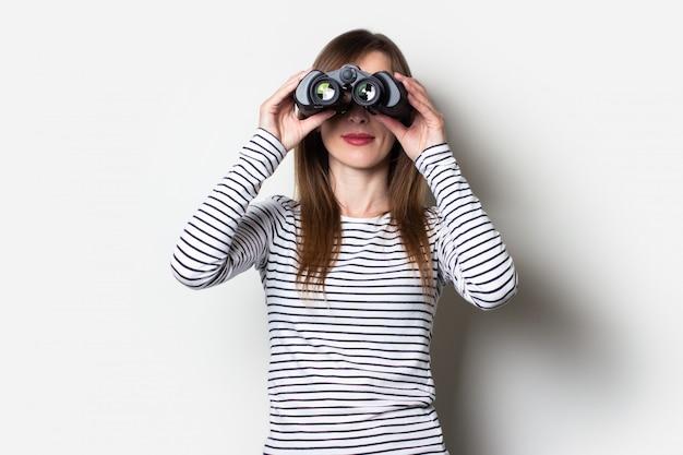 Młoda przyjazna dziewczyna patrząc przez lornetkę z tyłu na jasnej przestrzeni. transparent. emocjonalna twarz.