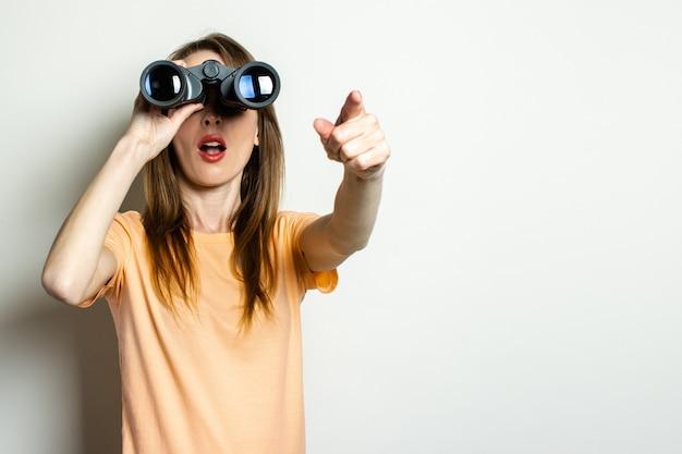 Młoda przyjazna dziewczyna patrzy przez lornetkę i wskazuje palcem na jasną przestrzeń. transparent. emocjonalna twarz.