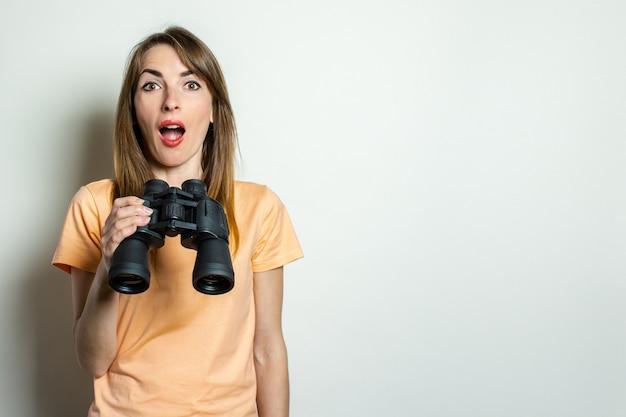 Młoda przyjazna dziewczyna z zaskoczoną twarzą w koszulce trzyma lornetkę na jasnej przestrzeni. transparent. emocjonalna twarz.