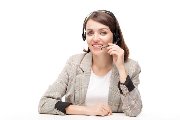 Młoda, przyjazna kobieta, operator telefonicznej infolinii patrzy na ciebie podczas konsultacji z jednym z klientów online