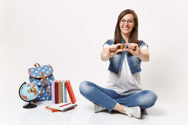 Młoda przyjemna piękna przypadkowa studentka w okularach trzymająca bitcoina siedząca w pobliżu kuli ziemskiej, plecaka, podręczników szkolnych na białym tle