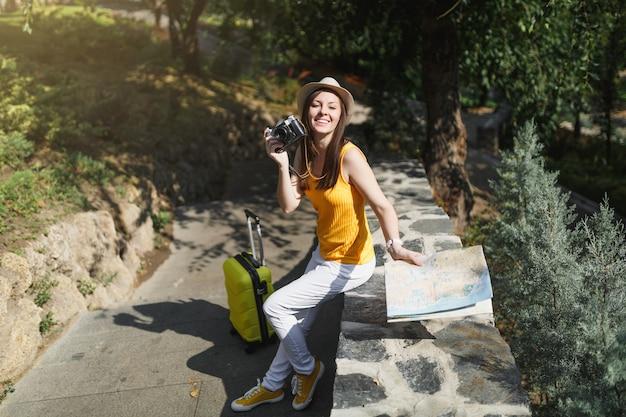 Młoda przyjemna podróżnik turystyczna kobieta w kapeluszu z walizką, mapa miasta trzymając aparat retro vintage zdjęcie w mieście na świeżym powietrzu. dziewczyna wyjeżdża za granicę na weekendowy wypad. styl życia podróży turystycznej.