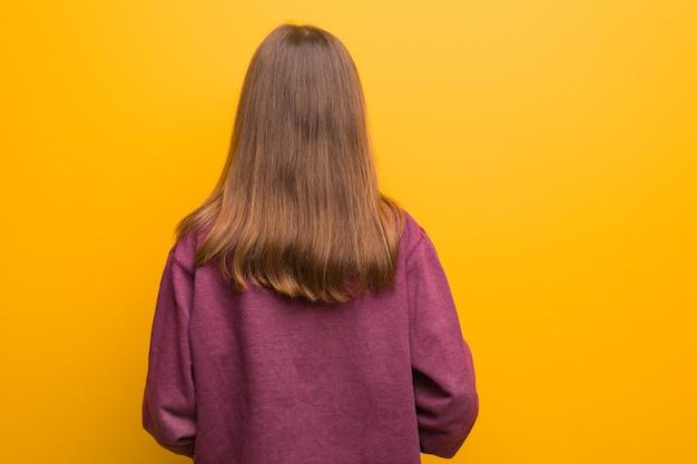 Młoda przypadkowa kobieta od tyłu, patrząc wstecz
