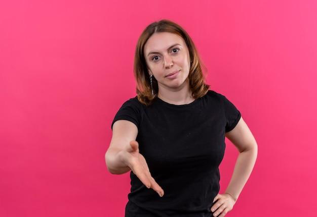 Młoda przypadkowa kobieta wyciągająca rękę, wskazująca cześć na odosobnionej różowej ścianie z miejsca na kopię