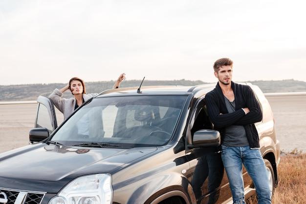 Młoda przypadkowa para stojąca przy swoim samochodzie nad morzem