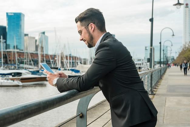 Młoda przystojna biznesmen pozycja blisko jeziora używać mądrze telefon