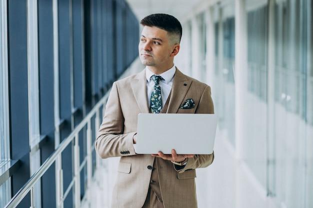 Młoda przystojna biznesowego mężczyzna pozycja z laptopem przy biurem