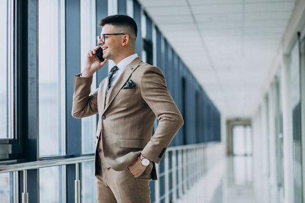 Młoda przystojna biznesowego mężczyzna pozycja z telefonem przy biurem