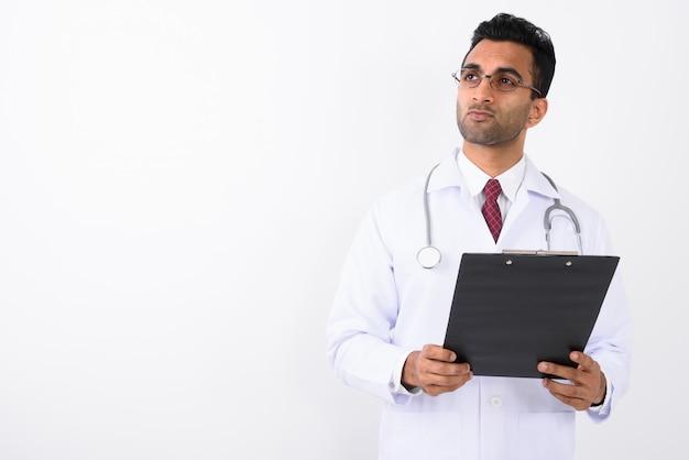 Młoda przystojna indiańska mężczyzna lekarka przeciw białemu tłu