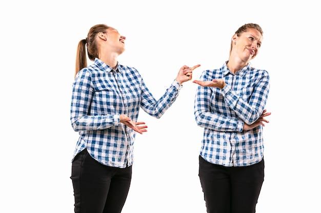 Młoda przystojna kobieta kłóci się ze sobą na tle białego studia.