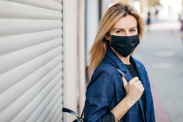Młoda Przystojna Kobieta Moda W Okularach Przeciwsłonecznych Z Plecakiem W Masce Przeciwpyłowej, Aby Chronić Się Przed Koronawirusem Chodzącym Po Mieście Premium Zdjęcia