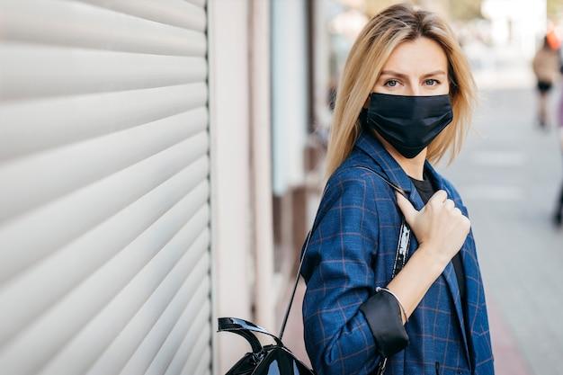 Młoda przystojna kobieta moda w okularach przeciwsłonecznych z plecakiem w masce przeciwpyłowej, aby chronić się przed koronawirusem chodzącym po mieście