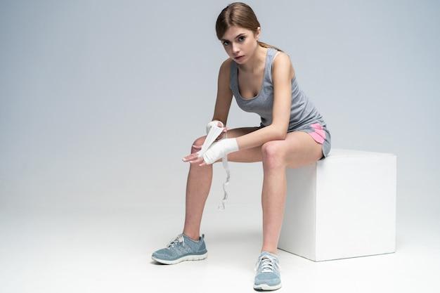 Młoda przystojna kobieta owijająca ręce zespołem, przygotowując się do treningu bokserskiego
