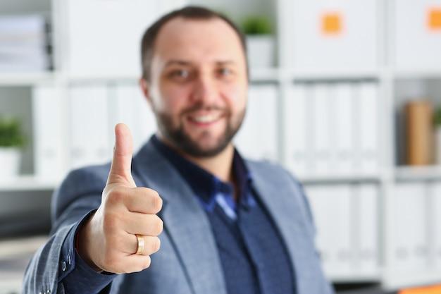 Młoda przystojna obiecująca biznesmen praca w biurowego przedstawienia dużym palcu up