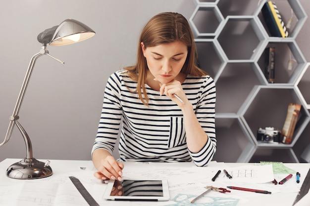 Młoda przystojna poważna inżynier dziewczyna z długimi brązowymi włosami w pasiastej koszuli, trzymając głowę ręką, patrząc w dokumenty z poważnym wyrazem twarzy, próbując znaleźć błąd w planach.