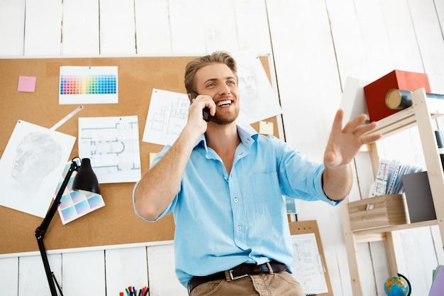 Młoda przystojna rozochocona ufna biznesmen pozycja przy stołem opowiada na telefonie. białe nowoczesne wnętrze biura