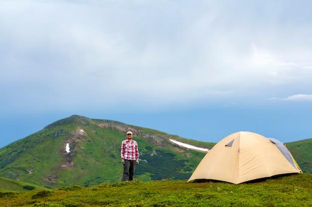 Młoda przystojna uśmiechnięta mężczyzna pozycja na zielonej trawiastej dolinie na słonecznym dniu przy małymi turystycznymi namiotowymi górami i jaskrawym niebieskiego nieba tłem. koncepcja turystyki, podróży, turystyki i aktywnego stylu życia.
