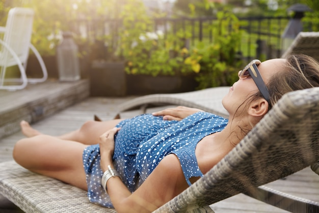 Młoda przyszła mama w okularach przeciwsłonecznych i letniej sukience śpi lub drzemie na leżaku, trzymając ręce na brzuchu.
