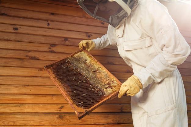 Młoda pszczelarka trzyma drewnianą ramę z plaster miodu, zbieraj miód, koncepcja pszczelarstwa,