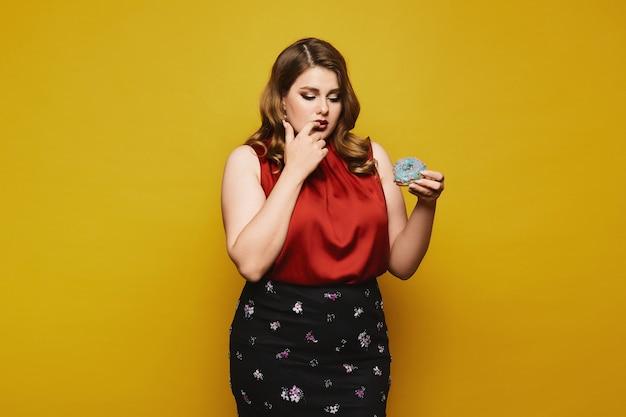 Młoda pulchna kobieta w czerwonej bluzce i czarnej spódnicy, trzymająca w dłoni smaczny pączek i patrząca na to, odizolowane