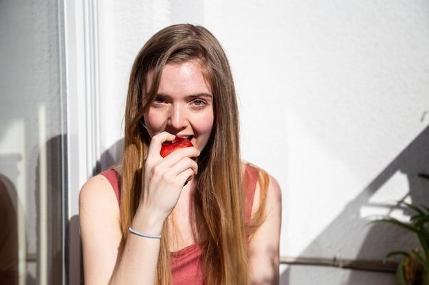 Młoda radosna atrakcyjna kobieta w swobodnej letniej sukience siedzi na balkonie i je smaczne soczyste czerwone jabłko