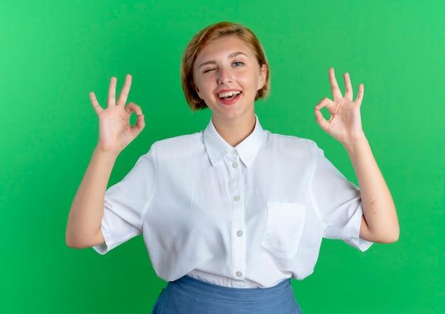 Młoda radosna blondynka rosjanka mruga okiem, wskazując ok znak dwiema rękami odizolowanymi na zielonym tle z miejsca na kopię