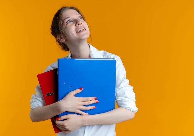 Młoda radosna blondynka rosjanka trzyma foldery plików patrząc w górę