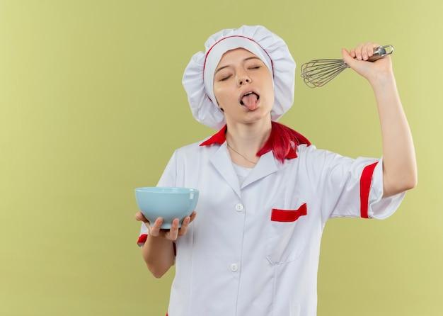 Młoda radosna blondynka szefa kuchni w mundurze szefa kuchni wystaje język z zamkniętymi oczami trzyma miskę i trzepaczkę na białym tle na zielonej ścianie