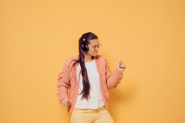 Młoda radosna brunetka w szkłach i hełmofonach na głowie ubierał w różowego puloweru białej bluzce i żółtych spodniach cieszy się muzykę i tanczy nad żółtym tłem z kopii przestrzenią.