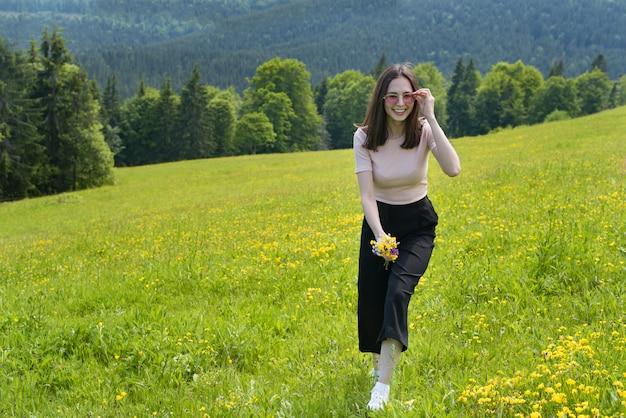 Młoda radosna kobieta chodzi na kwiat łące. letni słoneczny dzień.