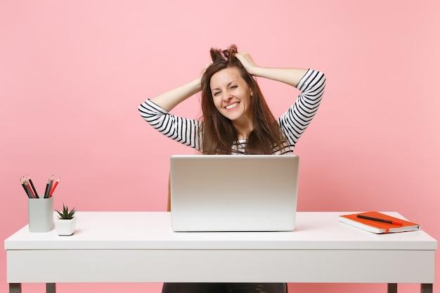 Młoda radosna kobieta przywiązana do włosów, głowa wykończenie pracy, kompletny projekt z laptopem pc, siedząc w biurze na białym tle na pastelowym różowym tle. koncepcja kariery biznesowej osiągnięcia. skopiuj miejsce.
