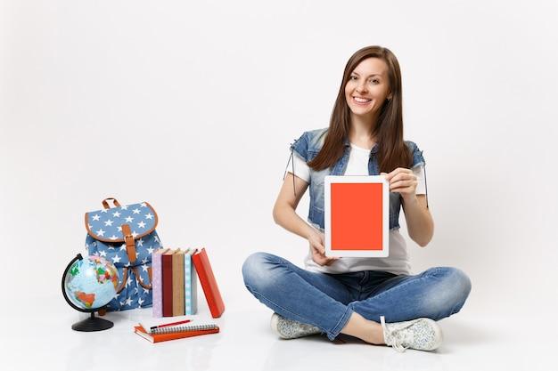 Młoda radosna kobieta studentka trzymająca komputer typu tablet z pustym czarnym pustym ekranem siedząca w pobliżu globu plecaka szkolne książki na białym tle