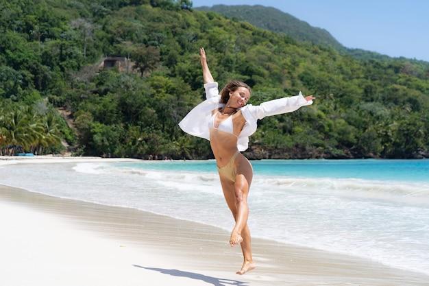 Młoda radosna kobieta w bikini i białej koszuli, ciesząc się morzem i wolnością. szczęście i beztroska koncepcja.
